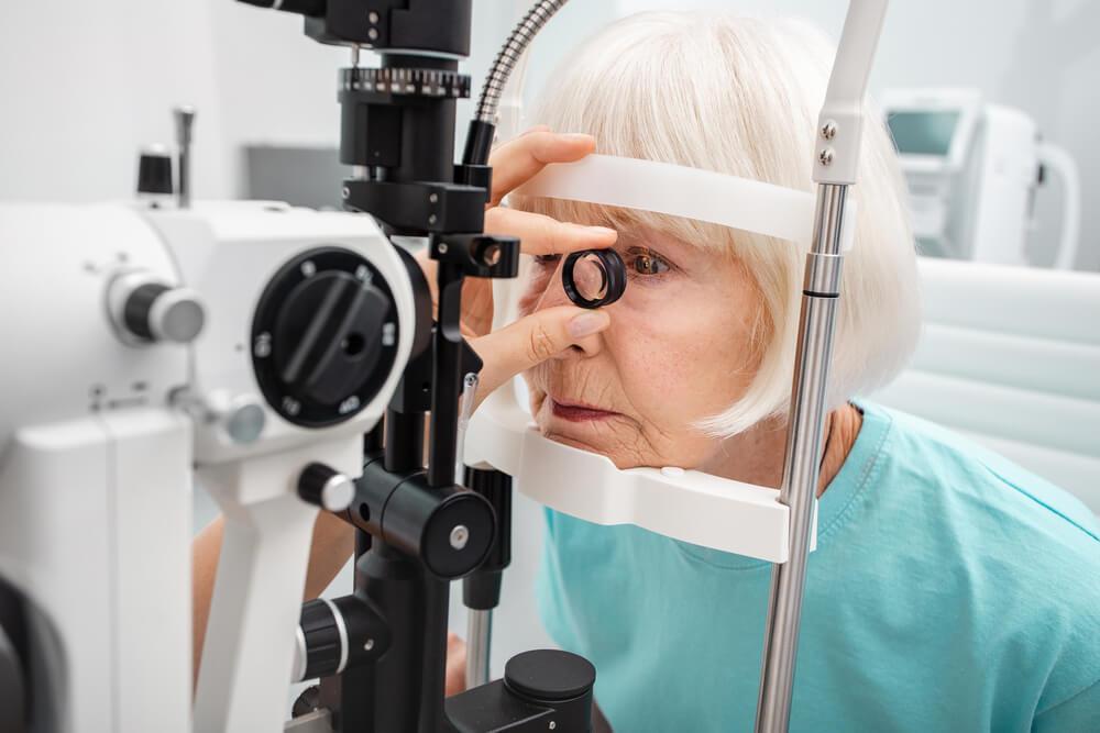 Senior woman eyesight test with binocular slit-lamp. Checking retina of a female eye close-up. Ophthalmology clinic